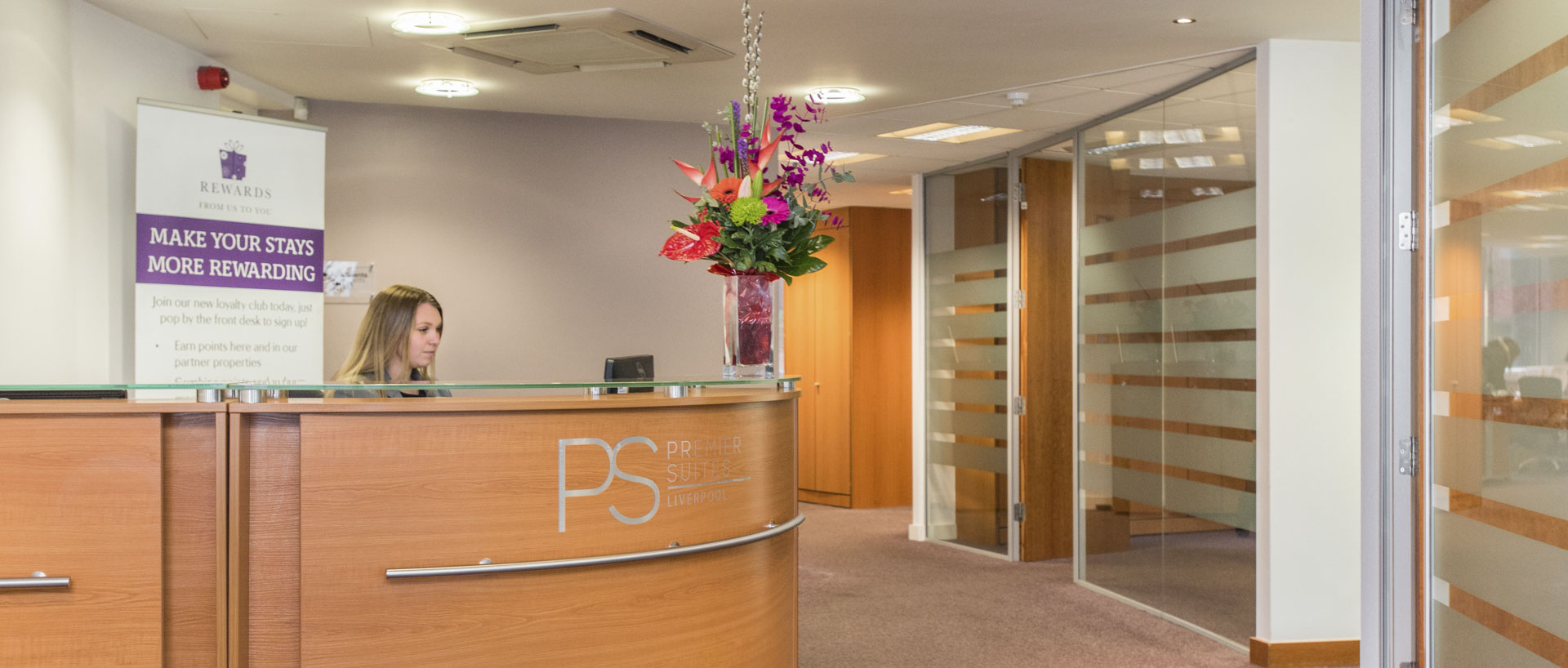 A receptionist at the front desk of PREMIER SUITES Liverpool